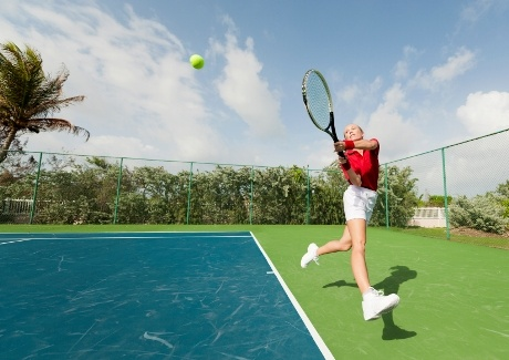 A young woman hitting a tennis shot, wide angle.