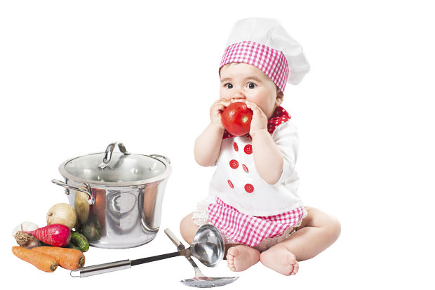 Baby girl wearing a chef hat with vegetables and pan. Use it for a child, healthy food concept