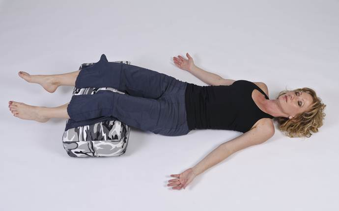 yoga poses for sciatica - supine with pillow under your knees